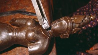 Incomplete wax sculpture being worked on by a pair of metal tweezers holding a small piece of dammar resin.