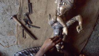 Sculptors carefully removing clay from the sculpture's face.