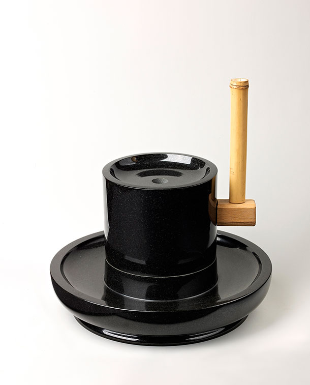 Shiny black granite hand mill with light wood handle. The mill's shape is like a bowl with a cylinder set perpendicular in the middle.