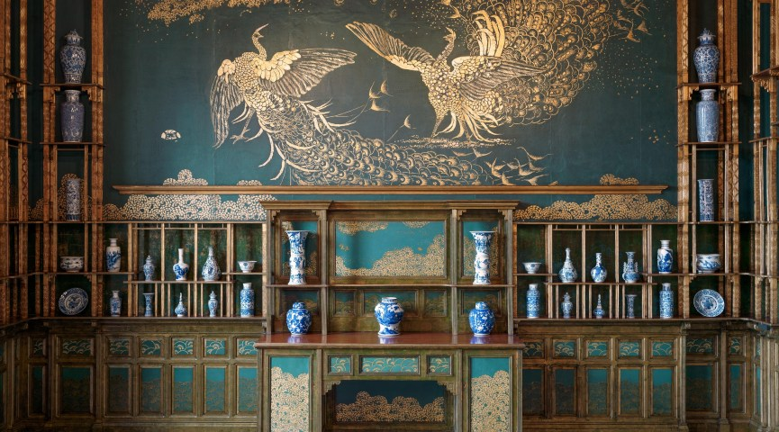 photograph of a large mural of two golden peacocks against a green background. gilded shelving holding numerous blue and white porcelain vessels surrounds the large mural