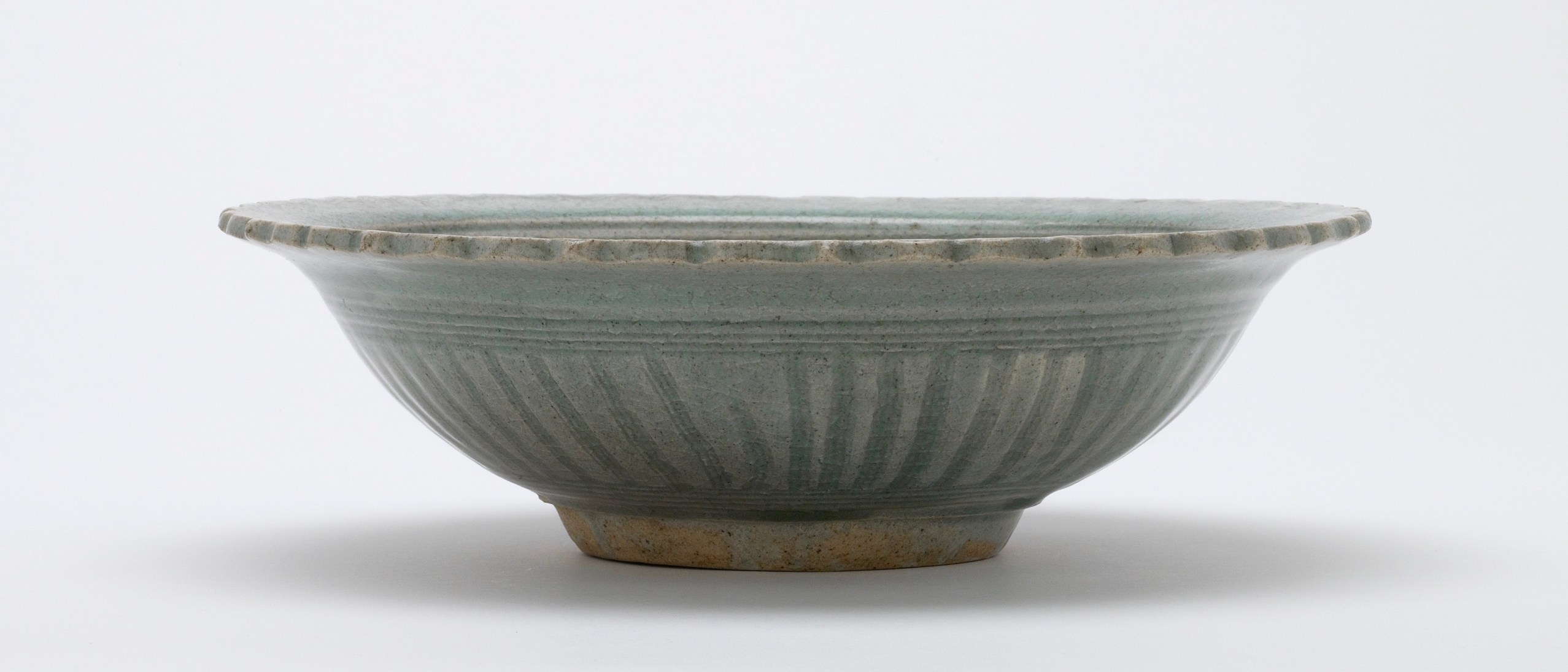 Stone bowl with celadon (pale blue-green) glaze; decorated with incisions and carvings