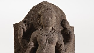 Stone sculpture of a standing figure (Durga), gazing at the viewer with a tranquil expression while standing on the defeated demon