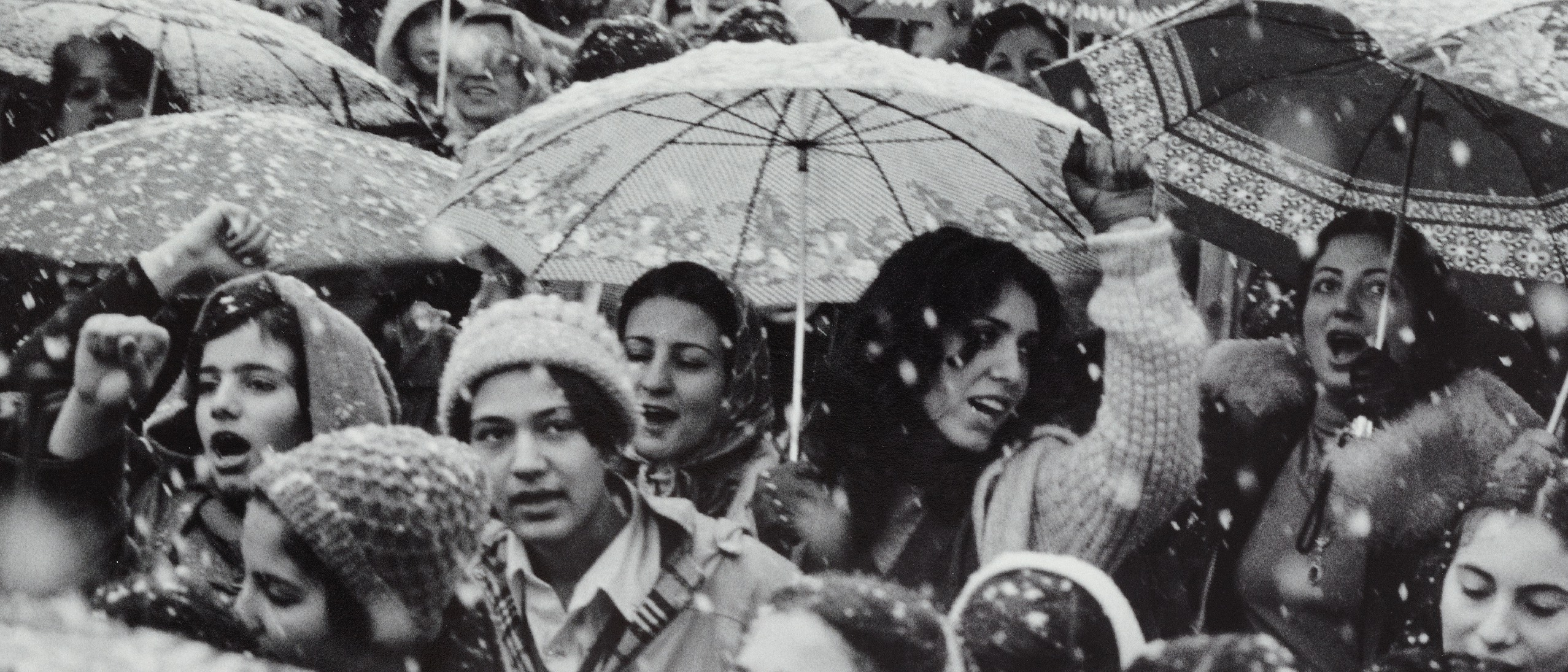 Black and white photo of a crowd with umbrellas and snow