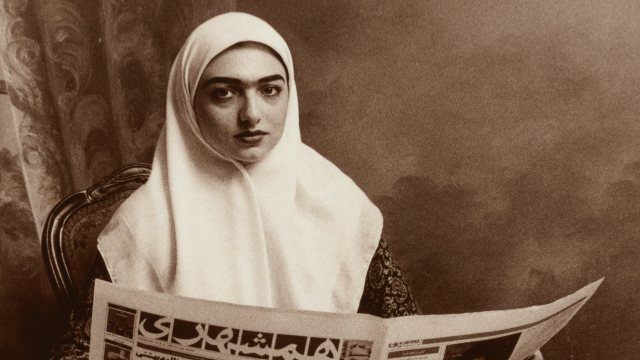 One woman reading news paper wearing a white turban