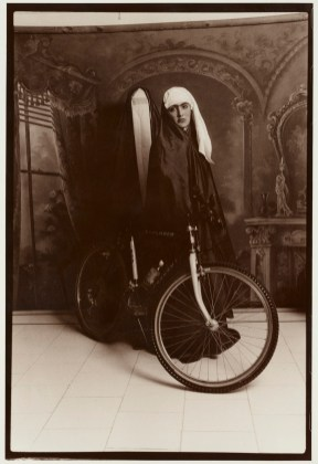 A woman with white turban next to bike
