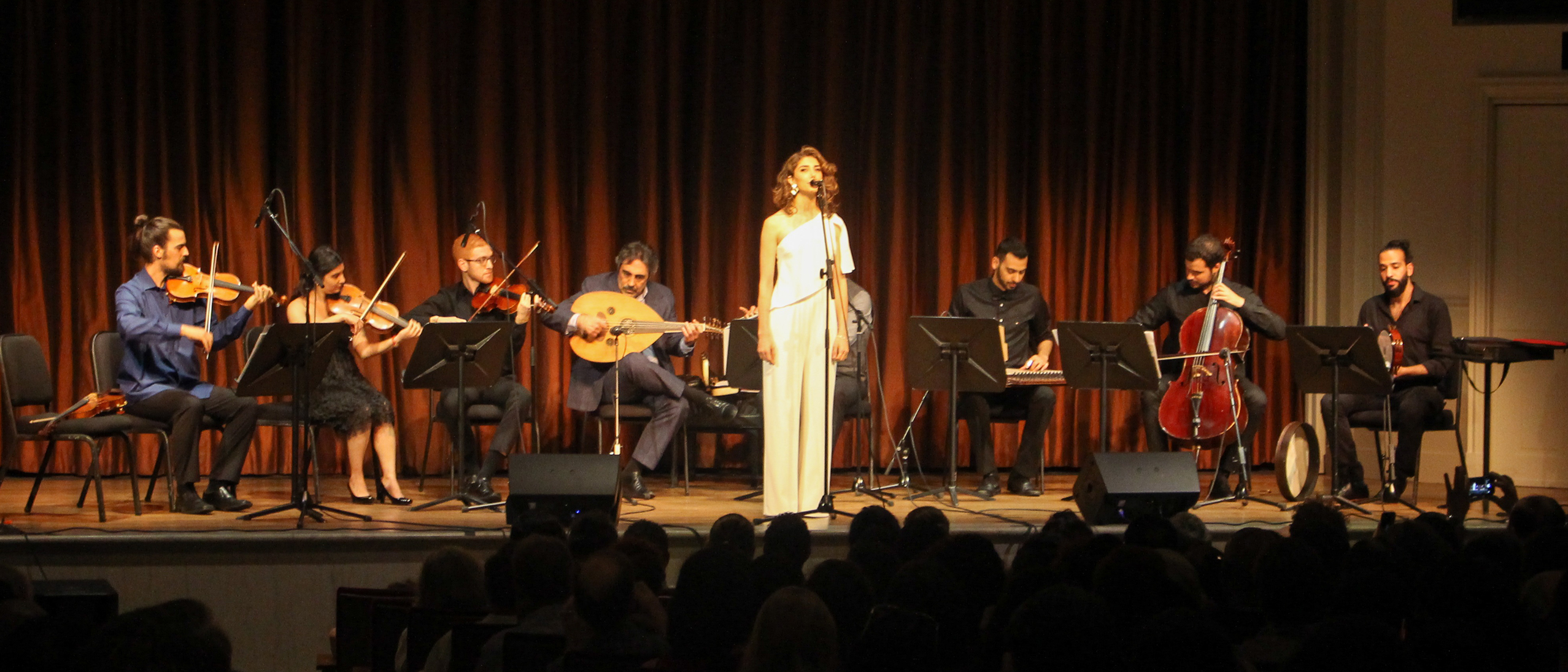 Woman in white jumpsuit sings on theater stage while surrounded by seven seated musicians.