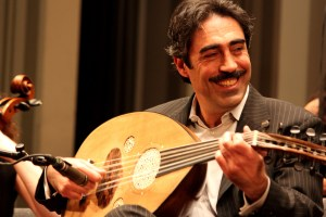 Man smiles while playing a lute.