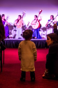 Little girl watches four musicians on stage.