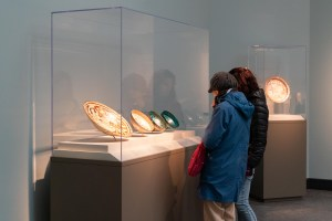 Two people in profile looking into a glass case with four round objects inside.