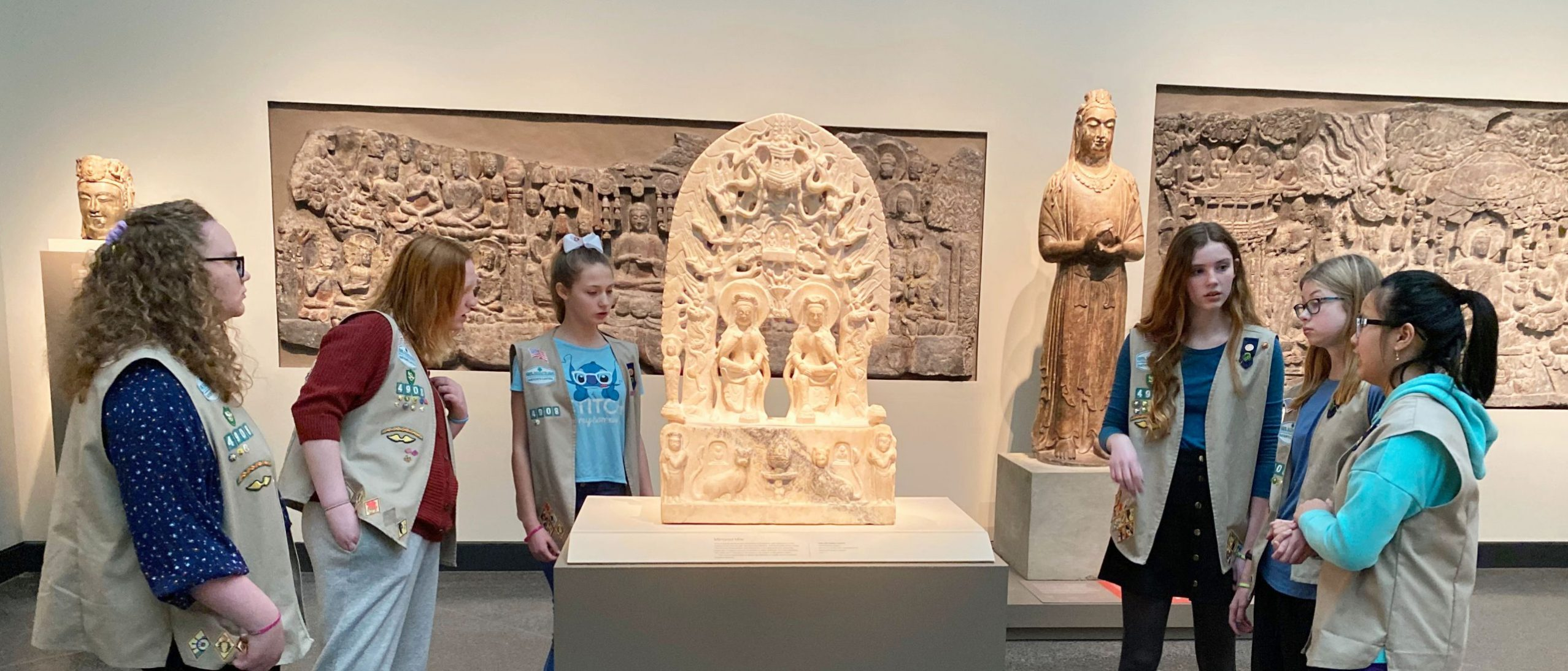 six girlscouts stand around a buddhist sculpture showing two figures on a pedastal with an elaborate arched backing above them. mounted in the wall behind the girls are two carved reliefs of buddhist scenes. also behind them are the head of a sculpture and a full sculpture standing