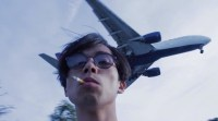 still from No Data plan, showing a person with a cigarette in their mouth, a plane flying in the sky just behind them