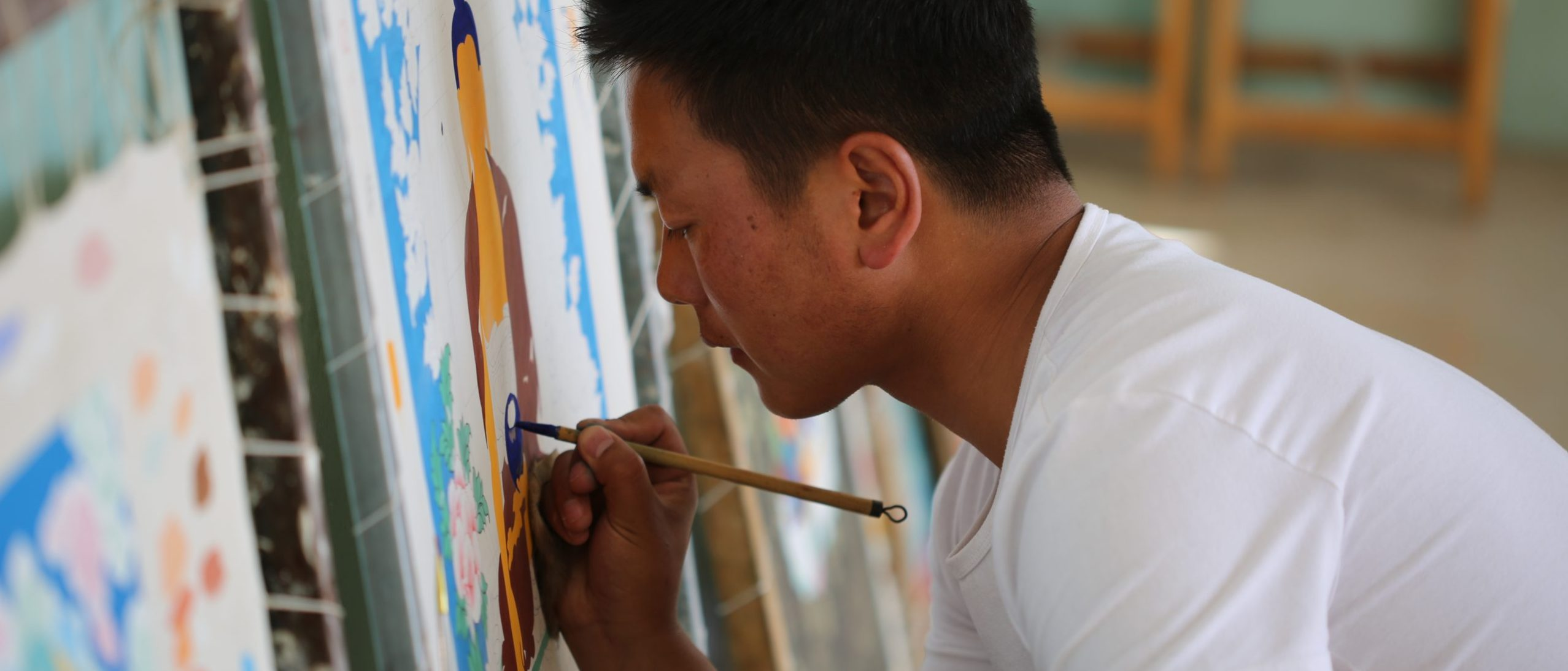 photo of a man painting on a canvas