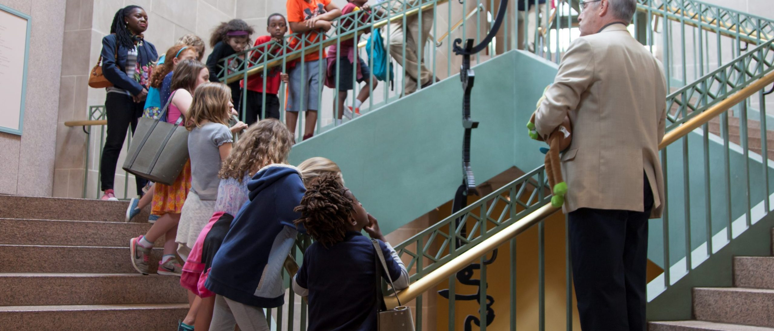 children on stairs in a museum observing artwork