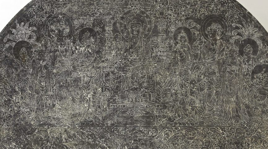 detailed etching of Buddist imagery on a flat circular stone
