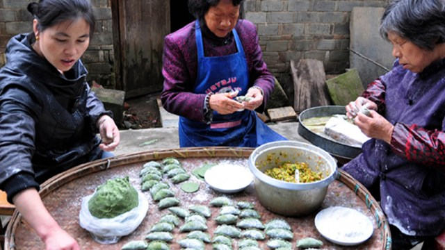 3 women prepare food on a table outdoors