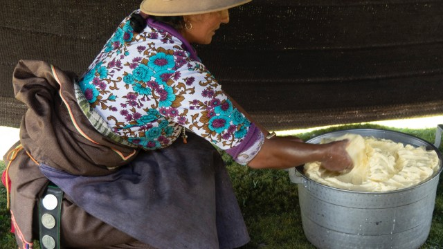 a woman stirs food in a large bowl