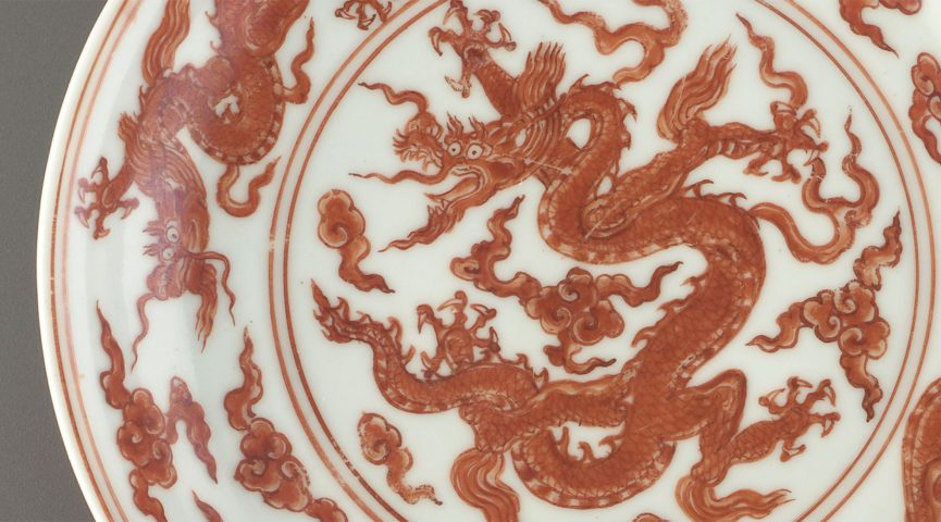 close up of red and white dragon design on pottery