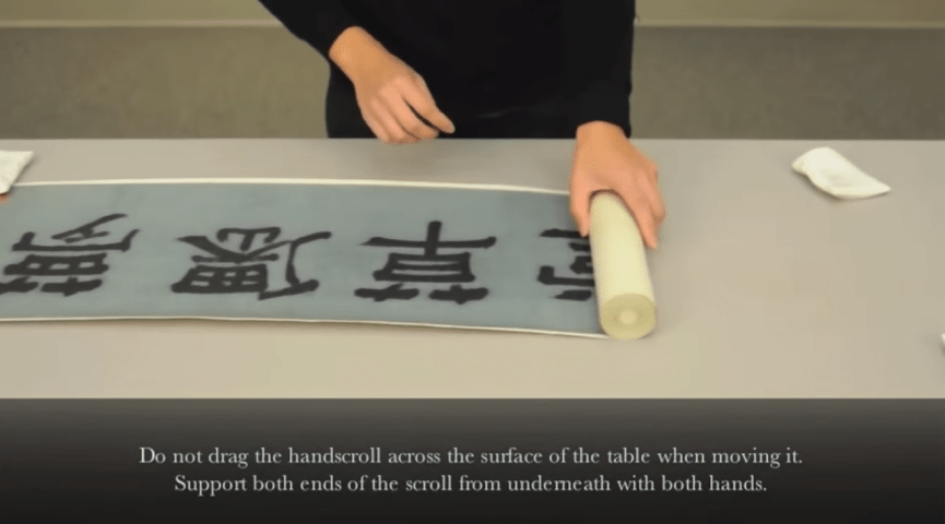 photo of hands unrolling a chinese scroll