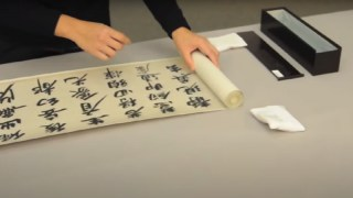 hands unrolling a scroll, with soft weights and a box next to it