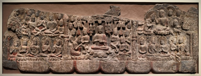 A large stone sculpture depicting a gathering of Buddhas and bodhisattvas removed from Cave Temples of Xiangtangshan and mounted for display.