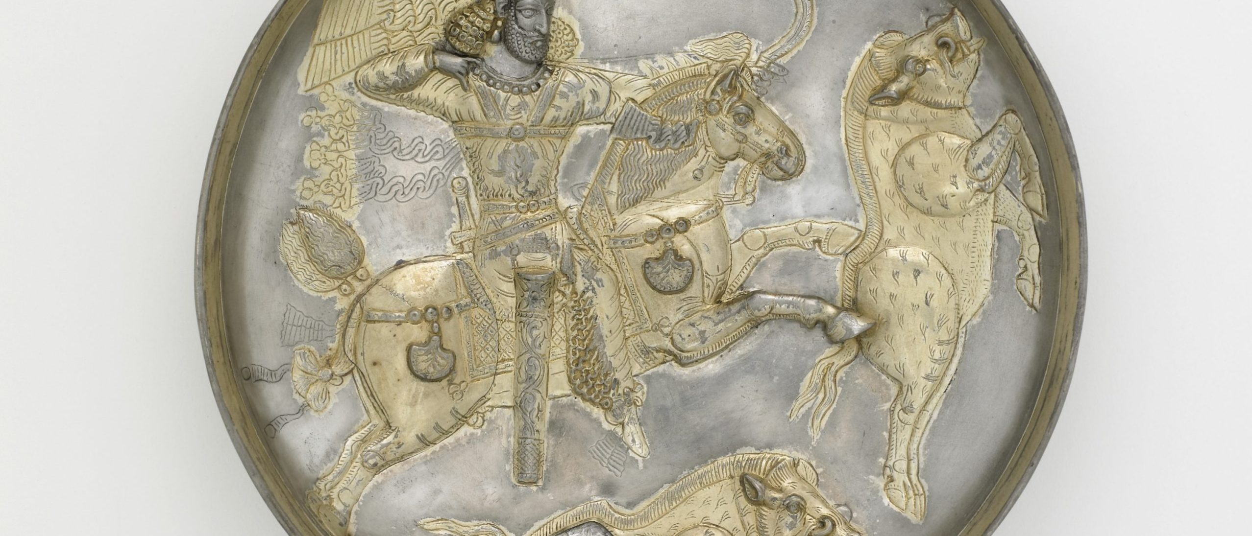 Metalwork plate with silver and gilt decoration with a hunting scene of a king on a horse aiming his bow and arrow at a boar, while another boar lays dead below the horse. The horse and the boar being chased look like they are leaping in mid-air. The king has his arm drawn back to indicate the arrow is notched and ready.