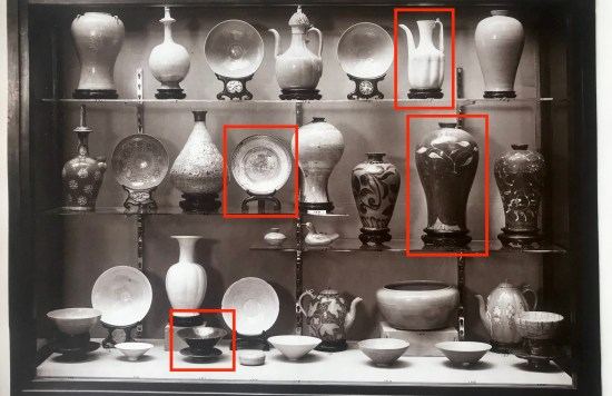 Black and white photo of a case of ceramics from the 1914 exhibition.