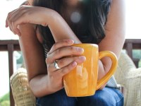 A person seated on a wicker chair on a deck with a yellow coffee mug in hand