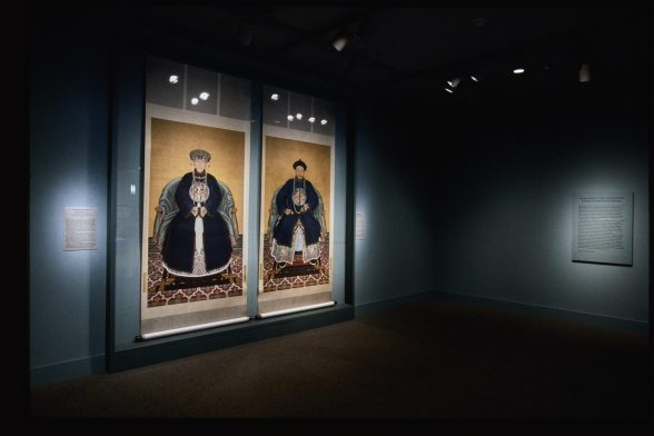 Two large Chinese ancestor portraits hang on a gallery wall in a starkly lit room painted blue