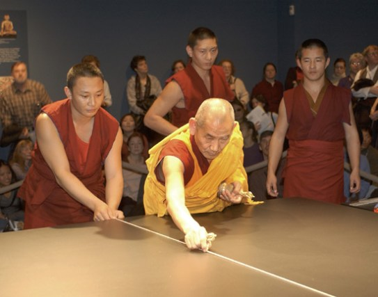 Young monks dressed in maroon assist and old monk clad in yellow to create the first guide line in white chalk on the table where the mandala will be created.