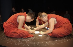 Three monks in red begin adding white sand to the center of the mandala. One stands, leaning far over the table, while two more sit cross-legged on top of the table.