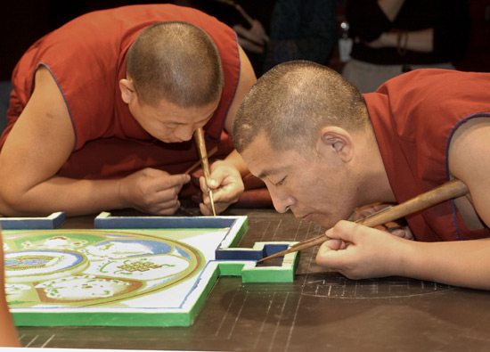 Two monks in red lean in close to the mandala. The center is already intricately drawn. They very steadily place sand upon a raised boarder surrounding the center of the mandala.