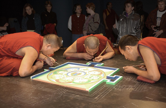 Three monks lean in close, working on the mandala.