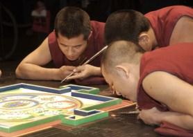 Close-up of several monks working on the mandala.