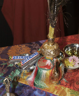 A spread of offerings, including a bowl of rice with flowers, an ornate gold centerpiece, and a bowl containing Snickers bars.