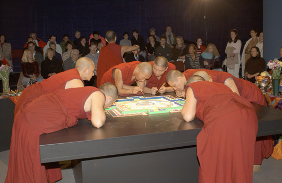 Six monks in red lean against the table to work on the mandala, while another monk faces and engages with a crowd behind them.