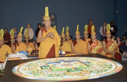 A monk in red and gold robes, wearing a yellow crested headdress chants over the finished mandala. Monks wearing the same clothes are seated in meditation behind him.