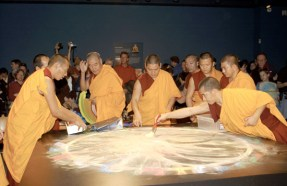 Several monks in red and gold robes stand around the table as the mandala is now completely destroyed by radial, even brushtrokes.