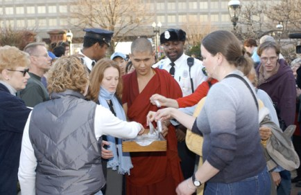 A monk in red distributes small bags of sand from the mandala to people outside the museum.