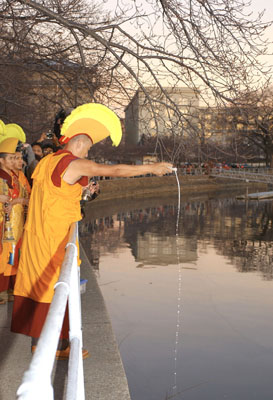 A monk in red and gold robes and a yellow crested headdress pours sand from the mandala into the Tidal Basin as the sun begins to set..
