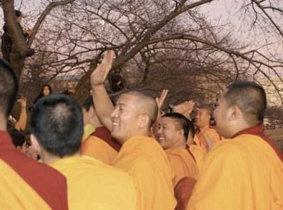 Monks wave joyously after the ceremony has been completed.