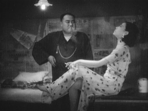 Black and white film still of two people blowing smoke from cigarettes, a man in black with a hand on his hip looks at woman in a long patterned dress as she leans back with one leg up.