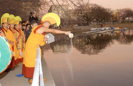Pouring a portion of the mandala's sand into the Tidal Basin to distribute healing energy around the world.