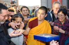 A monk distributes packets of sand from the dispersed mandala.