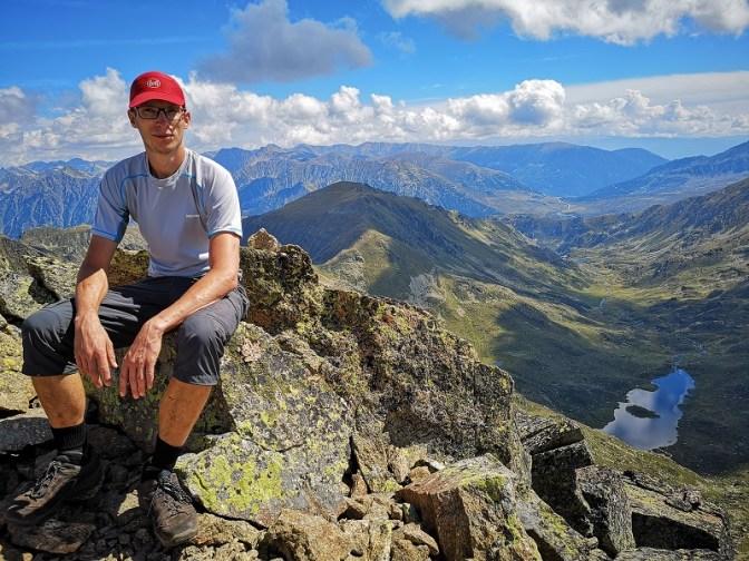 Mężczyzna siedzi na skale na szczycie góry Pic d'Escobes, za nim morze gór, Pireneje w Andorze