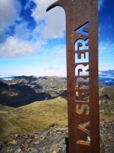 Widok na Pireneje, na pierwszym planie tabliczka z nazwą szczytu La Serrera, w Andorze
