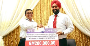 MOF official Shuhaimi Din presenting a mock cheque to Amarjit Singh Gill at Wadda Gurdwara Sahib Ipoh, Perak, today.