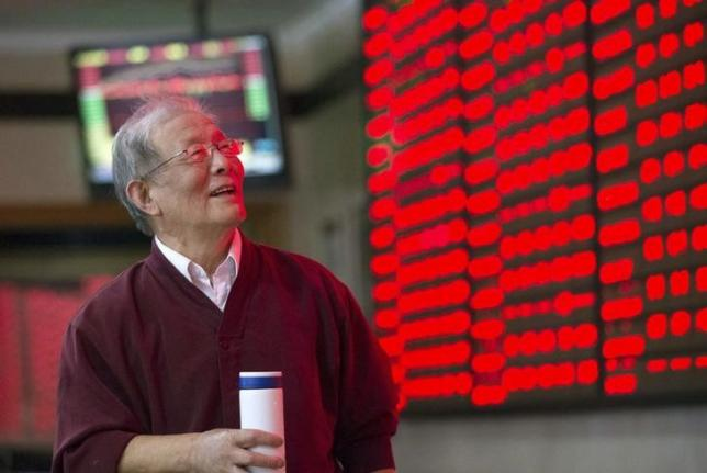 An investor looks at an electronic board showing stock information (red for gains) at a brokerage house in Nanjing, Jiangsu province, China. Photo: Reuters, China Daily