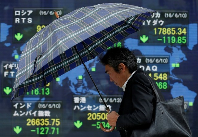 A pedestrian holding an umbrella walks past an electronic board showing the stock market indices of various countries outside a brokerage in Tokyo, Japan. Photo: Rueters