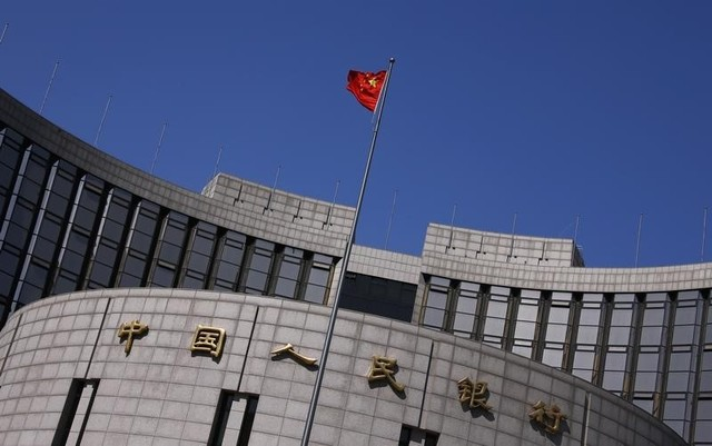 A Chinese national flag flutters outside the headquarters of the People's Bank of China, the Chinese central bank, in Beijing. Photo:   Reuters/Petar Kujundzic