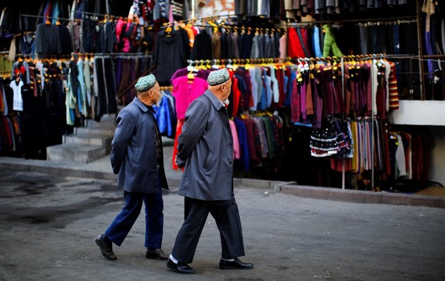 Two ethnic Uyghur men walk through a clothing market in downtown Urumqi in Xinjiang province in November 2013. Photo: Reuters.